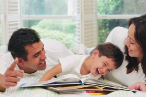 boy reading, laughing, mum, dad