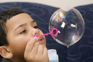Boy blowing bubble.